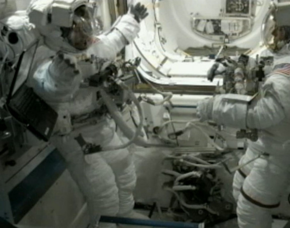 Endeavour shuttle astronaut Mike Fincke (left) stretches his arms while wearing a spacesuit during a spacewalk exercise test on May 25, 2011 before the third spacewalk of NASA's STS-134 mission to the International Space Station. The new excercises help remove nitrogen from spacewalkers' bodies to avoid developing the bends.