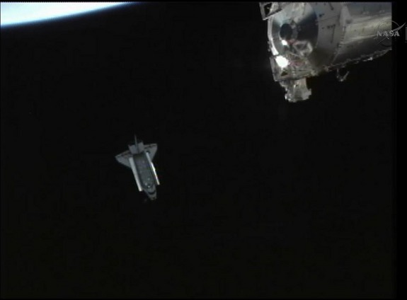 Shuttle Endeavour backs away from the International Space Station after undocking from the outpost for one last time on May 29, 2011 during the STS-134 mission. This view was recorded by a camera on the exterior of the space station, part of which is visible at bottom right