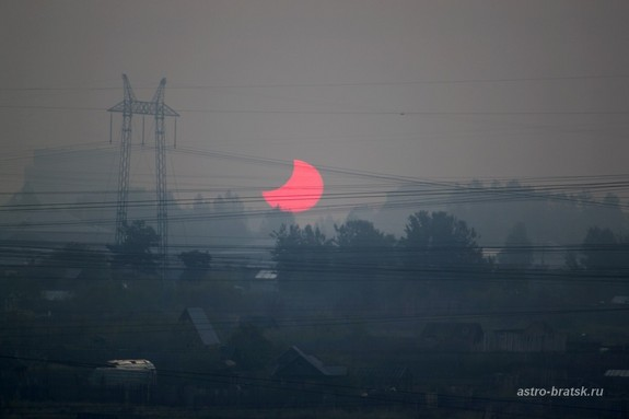 "Photographer and skywatcher Svetlana Kulkova snapped this view of the partial solar eclipse of June 1-2, 2011 just after sunrise on June 2 from Bratsk, Russia. The partial solar eclipse was dubbed a ""midnight"" eclipse as its viewing path crossed the International Date Line."