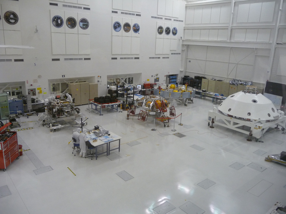 Pieces of NASA's Mars Science Laboratory mission at the Jet Propulsion Laboratory in May 2011. From left: the Curiosity rover (along rear wall; its tires are on a table to the rover's right), the entry-descent-landing stage, the cruise stage and the backshell.