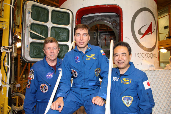 At the Baikonur Cosmodrome in Kazakhstan, NASA astronaut Mike Fossum (left), Expedition 28 flight engineer; cosmonaut and Soyuz commander Sergei Volkov (center) and Japan Aerospace Exploration Agency astronaut Satoshi Furukawa, flight engineer, pose for pictures outside their Soyuz TMA-02M spacecraft.