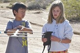 After having driven as far as possible, both on- and off-road, the DREAMS-11 payload recovery team conducts the final phase of its tracking operation on foot. Here Kenny Peng (l) and Lily Kelly use a Yagi-antenna radio beacon system and a road map of California to pinpoint the payload's landing site.