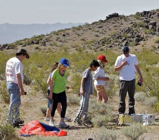 After a mile of cross-country hiking through the desert, the DREAMS-11 team locates the downed student balloon and its payload in April 2011. Left (blue and red-orange), the parachute; right (the gold and silver boxes), the payload.