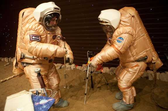 Crew training for 'Marswalk' at the simulated martian terrain of the Mars500 experiment. The terrain, about 10 m long and 6 m wide, is covered with reddish sand and is built to resemble the surface at Gusev crater. On the 'surface', they conducted simulated scientific research by driving a rover and working with sensors to gather physical and chemical measurements.