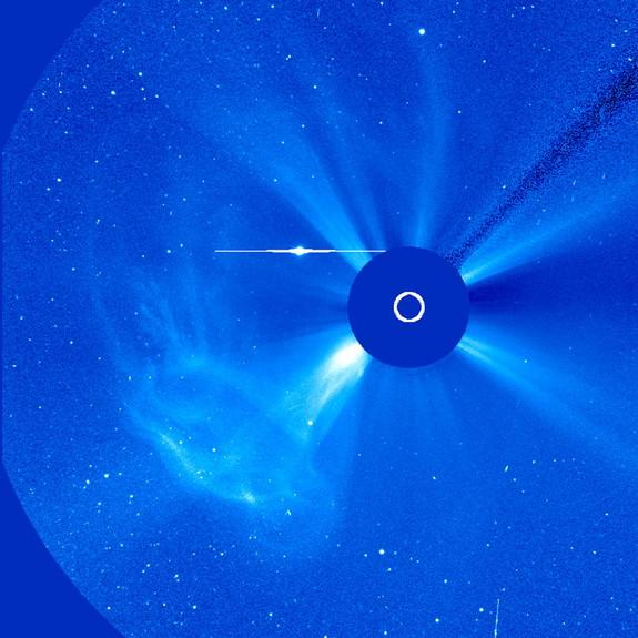 A broadly widening cloud of particles, observed by SOHO's C3 coronagraph, rushed away from the Sun as a coronal mass ejection (CME) erupted over about 12 hours (June 14, 2011). Data from the Solar Dynamics Observatory shows an eruptive prominence breaking away from the Sun about where the event originated. While the originating event did not appear to be substantial, the particle cloud was pretty impressive. The bright circle with an extending horizontal line (above and left of the blue occulting disk) is a distortion caused by the brightness of planet Mercury.
