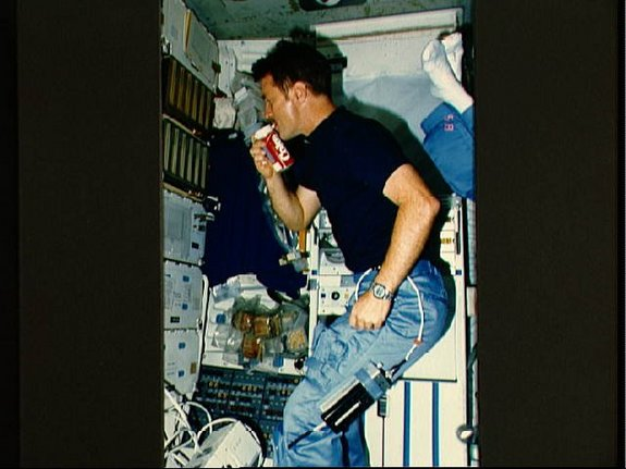 Astronaut Anthony W. England, mission specialist, drinks from a special carbonated beverage dispenser labeled Coke while floating in the middeck area of the shuttle Challenger during the STS-51F mission in 1985. Note the can appears to have its own built in straw.