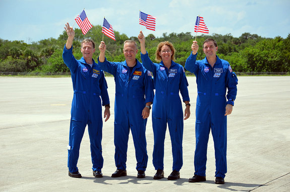 NASA's final space shuttle crew waves American flags celebrating their Fourth of July arrival at Kennedy Space Center for their launch on July 8, 2011. From left to right: Commander Chris Ferguson, Pilot Doug Hurley and mission specialists Sandy Magnus and Rex Walheim.