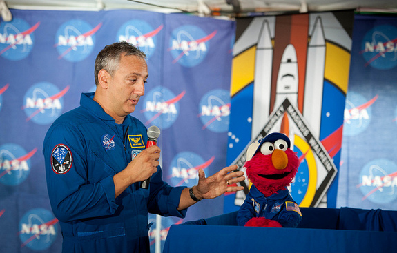 NASA astronaut Mike Massimino, left, and Sesame Street's Elmo speak at the STS-135 Tweetup on July 7, 2011 at Kennedy Space Center in Cape Canaveral, Fla. Elmo asked the astronauts questions about living and working in space.