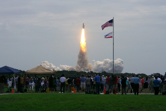Spectators in the foreground watch as Atlantis launches on its final flight, July 8, 2011.