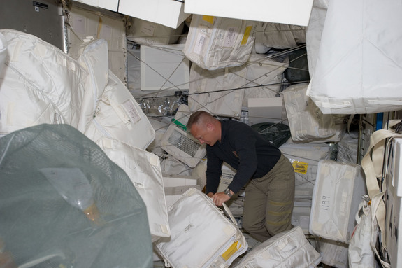 NASA astronaut Doug Hurley, STS-135 pilot, moves around supplies and equipment in the Leonardo Permanent Multipurpose Module (PMM) on July 11, 2011 during the fourth day of flight for Atlantis' four person crew.