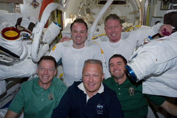 Following the 6 1/2-hour spacewalk of NASA astronauts Ron Garan (top left) and Mike Fossum (top right) on July 12, 2011, five members of the joint shuttle-station crew pose for photographs in the Quest airlock of the International Space Station. Remaining inside but contributing greatly to the outside duo were, from left front, NASA astronauts Chris Ferguson, STS-135 commander, Doug Hurley, pilot, and Rex Walheim, mission specialist. Garan and Fossum are flight engineers for the station's Expedition 28 crew.  It was the last spacewalk of NASA's shuttle era and performed during the STS-135 shuttle mission.