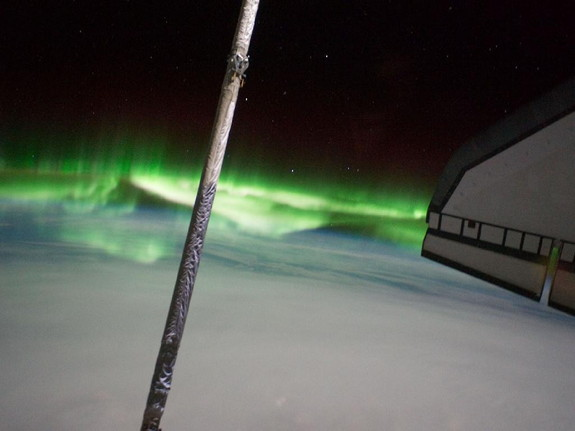 One of the STS-135 Atlantis crewmembers took this photo of the Southern Lights or Aurora Australis while visiting the International Space Station on July 14, 2011. Part of the orbiter boom sensor system (OBSS) is seen, as it was attached on the end of the shuttle's robotic arm (out of frame). A part of the port side wing of the shuttle is at right and a solar panel for the station is at left edge.