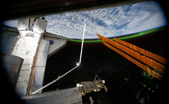 This panoramic view from the International Space Station, looking past the docked shuttle Atlantis' cargo bay and part of the station including a solar array panel toward Earth, was taken on July 14, 2011 as the spacecraft passed over the Southern Hemisphere. Aurora Australis or the Southern Lights can be seen on Earth's horizon and a number of stars are visible also.