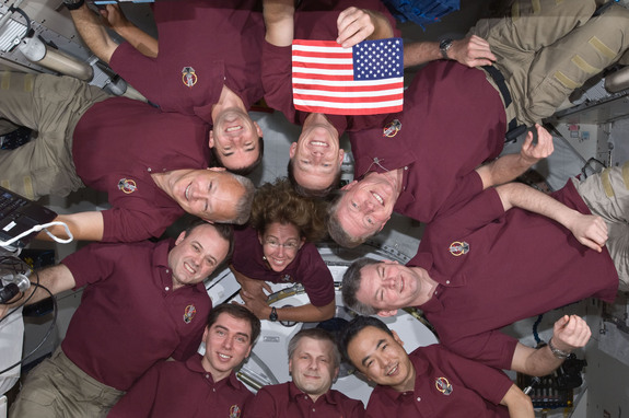 The 10 combined crewmembers of STS-135 and Expedition 28 pose with the STS-1 flag aboard the International Space Station. The flag flew on NASA's first shuttle mission in 1981, and the final flight STS-135 in July 2011.