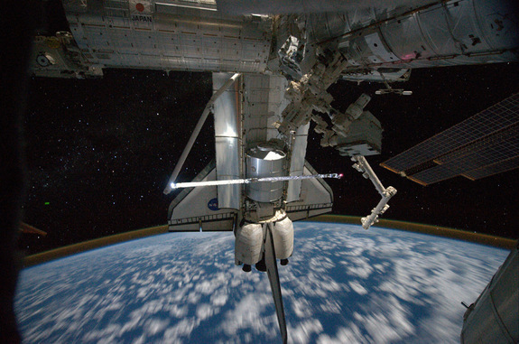 "This view of the space shuttle Atlantis while still docked with the International Space Station was taken by a crew member aboard the station on the final day of joint activities between the crew members for the STS-135 and Expedition 28 missions. The robotic arm on the shuttle appears to be saluting ""good-bye"" to the station. Earth's airglow is seen as a thin blue line above Earth's horizon. The Raffaello multi-purpose logistics module, full of items to be returned to Earth, is seen in the aft cargo bay, July 19. 2011. Flight Day 12."