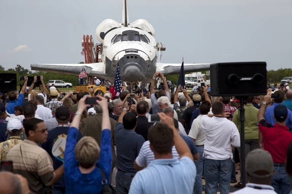 Space shuttle Atlantis is slowly towed from the Shuttle Landing Facility to an orbiter processing facility at NASA's Kennedy Space Center in Florida for the last time on July 21, 2011. A crowd of NASA workers is on hand for an employee appreciation event.