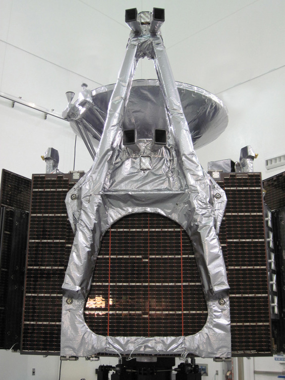 The Juno spacecraft, folded up and awaiting encapsulation in the rocket fairing. The 13-foot-long magnetometer boom, wrapped in bright thermal blankets, is in the foreground atop a stack of folded solar arrays. One of the twin magnetometers is mounted in the middle of the boom, and the other is mounted at the outermost end. Next to each magnetometer sensor is a pair of rectangular hoods, or light baffles, peeking out from under the thermal blankets; these define the fields of view for the two star cameras, which determine the orientation of each magnetometer sensor with great accuracy.