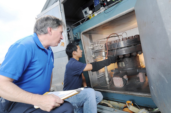 Paul Steffes and Danny Duong, both of Georgia Tech, examine the instrumentation on a machine used to simulate atmospheres on alien planets.