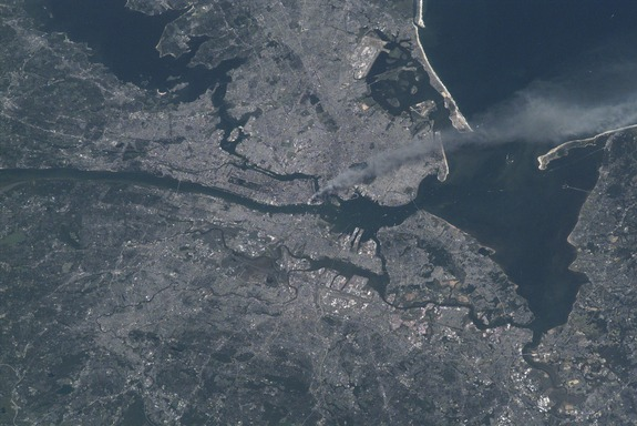 One of a series of pictures of metropolitan New York City taken by one of the Expedition Three crew members onboard the International Space Station (ISS) at various times during the day on September 11, 2001. A smoke plume rises from the Manhattan area where the World Trade Center was destroyed. The orbital outpost was flying at an altitude of approximately 250 miles.