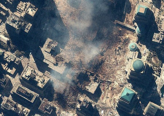 Space Imaging's IKONOS satellite collected this image of Manhattan, New York at 11:54 a.m. EDT on Sept. 15, 2001. The image shows the remains of the 1,350-foot towers of the World Trade Center, and the debris and dust that settled throughout the area. Also visible are many emergency and rescue vehicles in the streets. IKONOS orbits 423 miles above the Earth's surface at a speed of 17,500 miles per hour.