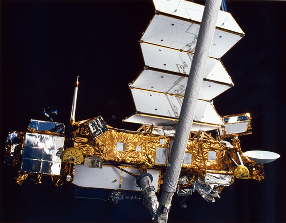 The Upper Atmosphere Research Satellite hangs in the grasp of the Remote Manipulator System against the blackness of space during deployment from Space Shuttle Discovery, September 1991.