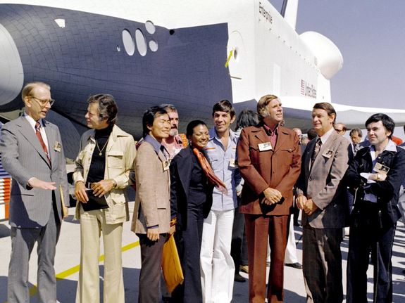 "In 1976, NASA's space shuttle Enterprise rolled out of the Palmdale manufacturing facilities and was greeted by NASA officials and cast members from the 'Star Trek' television series. From left to right they are: NASA Administrator Dr. James D. Fletcher; DeForest Kelley, who portrayed Dr. ""Bones"" McCoy on the series; George Takei (Mr. Sulu); James Doohan (Chief Engineer Montgomery ""Scotty"" Scott); Nichelle Nichols (Lt. Uhura); Leonard Nimoy (Mr. Spock); series creator Gene Roddenberry; an unnamed NASA official; and, Walter Koenig (Ensign Pavel Chekov)."