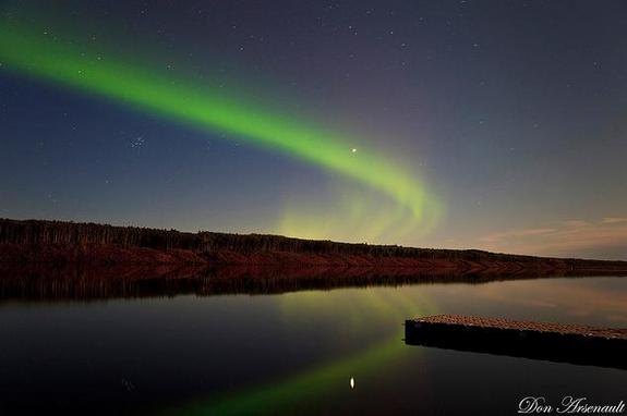 A wisp of aurora arcs over a serene lake in this spectacular photo captured by skywatcher and photographer Don Arsenault on Sept. 10, 2011 during a dazzling northern lights display.