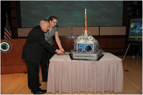 National Reconnaissance Office Director Bruce Carlson and cake design winner, Alli Taylor, cutting the official NRO birthday cake to mark the 50th anniversary of the U.S. space surveillance agency..