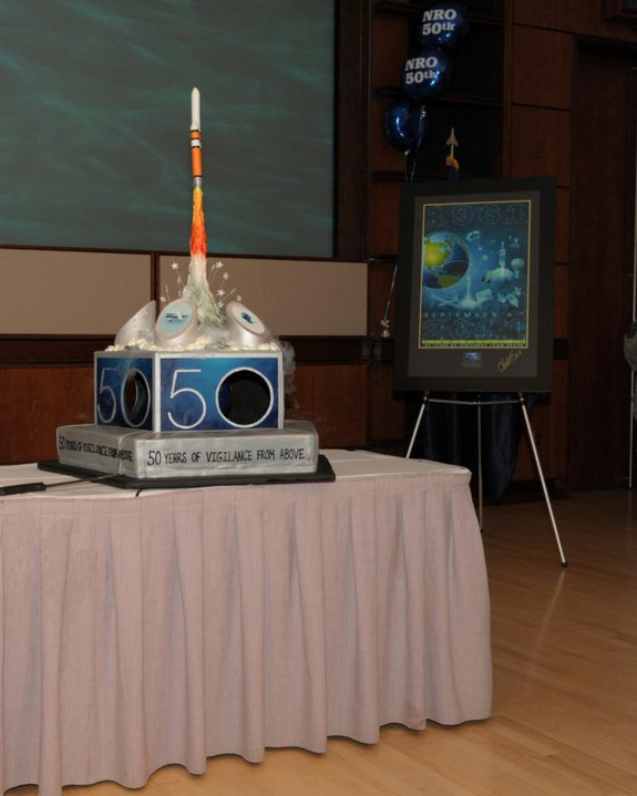 The National Reconnaissance Office's 50th Anniversary cake and commemorative poster to mark the Sept. 9 founding of the U.S. spy satellite agency.