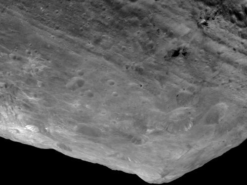 In this image of the south pole region of the asteroid Vesta, a mountain is rising approximately 9 miles (15 kilometers) above the floor of a crater.