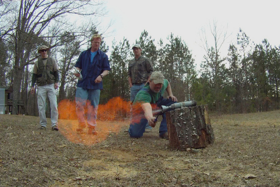 Rog ignites a test rocket using the gangs moonshine which Travis holds in the background