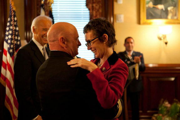 Captain Mark Kelly hugs his wife Congresswoman Gabrielle Giffords after receiving the Legion of Merit from Vice President Joe Biden during Captain Kelly's retirement ceremony in the Secretary of War Suite in the Eisenhower Executive Office Building, in Washington, D.C., Oct. 6, 2011.