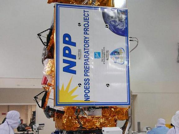 In a clean room inside the Astrotech Payload Processing Facility at Vandenberg Air Force Base in California, Ball Aerospace technicians rotate NASA's National Polar-orbiting Operational Environmental Satellite System Preparatory Project (NPP) spacecraft into the vertical position during a solar array frangible bolt pre-load verification test.