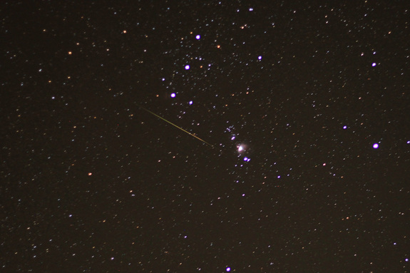 An Orionid meteor streaks across the sky, with the bright three-star belt of the constellation Orion, as well as the Orion nebula (center right) shine in the background. This image was taken before sunrise on Oct. 22, 2011 from Ozark, Ark., during the peak of the 2011 Orionid meteor shower.