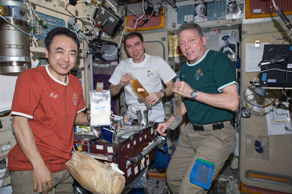 NASA astronaut Mike Fossum (right), Expedition 29 commander, along with Japan Aerospace Exploration Agency astronaut Satoshi Furukawa (left) and Russian cosmonaut Sergei Volkov, both flight engineers, share a meal at the galley in the Zvezda Service Module of the International Space Station on Sept. 16, 2011
