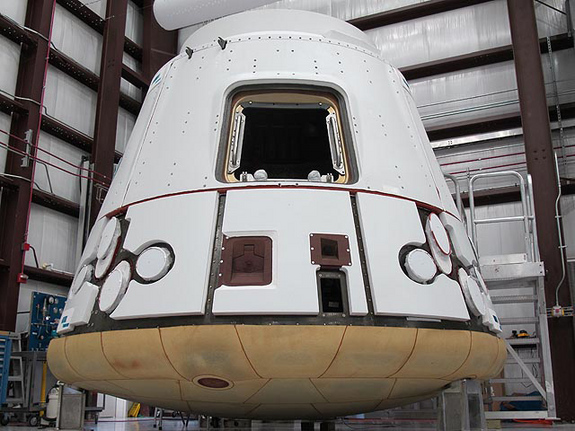 In the SpaceX hangar at Cape Canaveral, the Dragon spacecraft prepares for integration with the Falcon 9 launch vehicle. Visible at the base of the spacecraft is Dragon's heat shield, made of PICA-X, the SpaceX manufactured variation on NASA's Phenolic Impregnated Carbon Ablator (PICA) heat shield material. Dragon will reenter the Earth's atmosphere at around 7 kilometers per second (15,660 miles per hour), heating the exterior up to 1850 degrees Celsius. However, just a few inches of the PICA-X material will keep the interior of the spacecraft at a comfortable temperature.