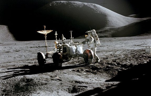 Astronaut James B. Irwin, lunar module pilot, works at the Lunar Roving Vehicle during the first Apollo 15 lunar surface extravehicular activity at the Hadley-Apennine landing site.