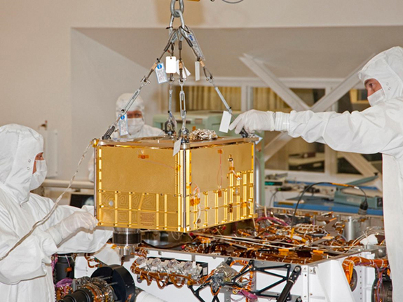 Technicians and engineers carefully install the 88-pound (40-kilogram) SAM instrument on the Curiosity rover. The picture was taken at NASA's Jet Propulsion Laboratory, Pasadena, Calif., on Jan. 6, 2011.