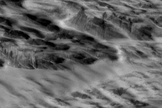Martian terrain with dark streaks interpreted as avalanches blasted by shockwaves from a meteorite impact are visible in this photo from NASA's Mars Reconnaissance Orbiter.