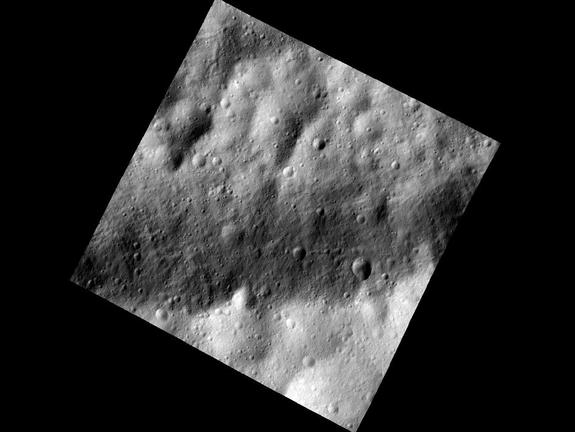 This close-up photo of the asteroid Vesta taken by NASA's Dawn spacecraft shows a part of one of the troughs at the equator of the asteroid. In the image, the floor of one of the equatorial troughs appears as the brighter deposit at the bottom of this image, contrasted against the darker band of the trough edge.