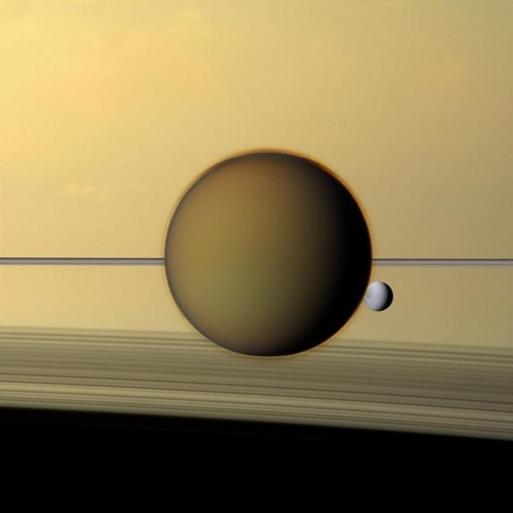 Saturn's third-largest moon Dione can be seen through the haze of its largest moon, Titan, in this view of the two posing before the planet and its rings from NASA's Cassini spacecraft released on Dec. 22, 2011. The north polar hood can be seen on Titan appearing as a detached layer at the top of the moon here.