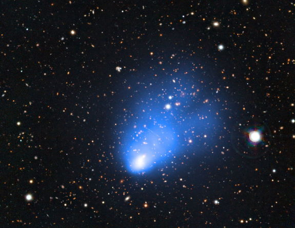 "This picture of the galaxy cluster ACT-CL J0102-4915 combines images taken with ESO's Very Large Telescope with images from the SOAR Telescope and X-ray observations from NASA's Chandra X-ray Observatory. The X-ray image shows the hot gas in the cluster and is shown in blue. This newly discovered galaxy cluster has been nicknamed El Gordo — the ""big"" or ""fat one"" in Spanish. It consists of two separate galaxy subclusters colliding at several million kilometres per hour, and is so far away that its light has travelled for seven billion years to reach the Earth."