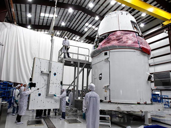 Dragon's solar array panels being installed on Dragon's trunk at the SpaceX hangar in Cape Canaveral, Fla.