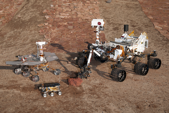 This grouping of two test rovers and a flight spare provides a graphic comparison of three generations of Mars rovers developed at NASA's Jet Propulsion Laboratory, Pasadena, Calif. The setting is JPL's Mars Yard testing area.  Front and center is the flight spare for the first Mars rover, Sojourner, which landed on Mars in 1997 as part of the Mars Pathfinder Project. On the left is a Mars Exploration Rover Project test rover that is a working sibling to Spirit and Opportunity, which landed on Mars in 2004. On the right is a Mars Science Laboratory test rover the size of that project's Mars rover, Curiosity, which is on course for landing on Mars in August 2012.