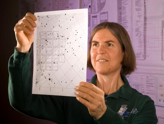 Janice Voss, a scientist who worked on Kepler, studies a field plate, or identifier.