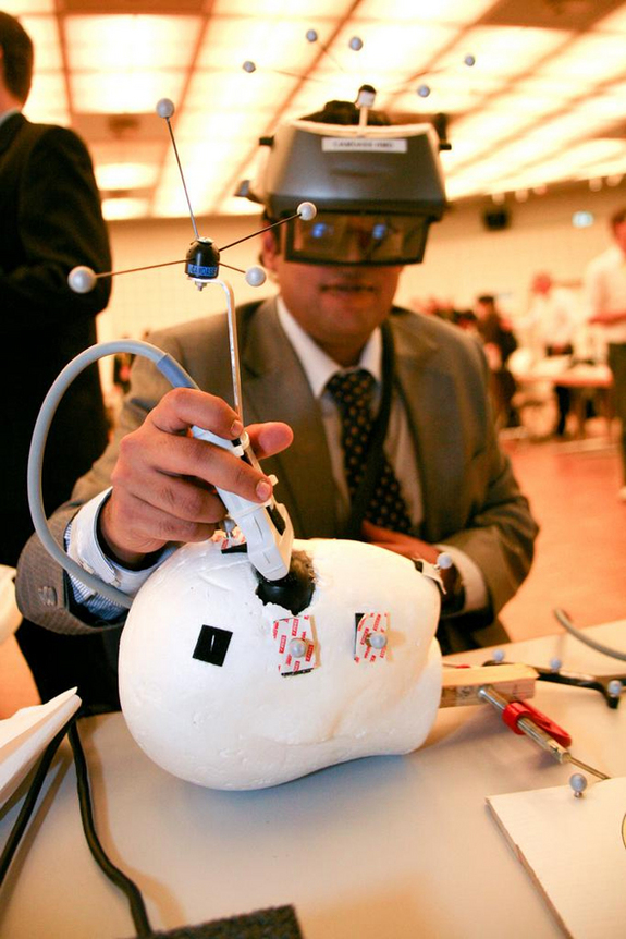 The CAMDASS headset being tried out on a plastic head during the October 2011 International Symposium on Mixed and Augmented Reality in Basel, Switzerland