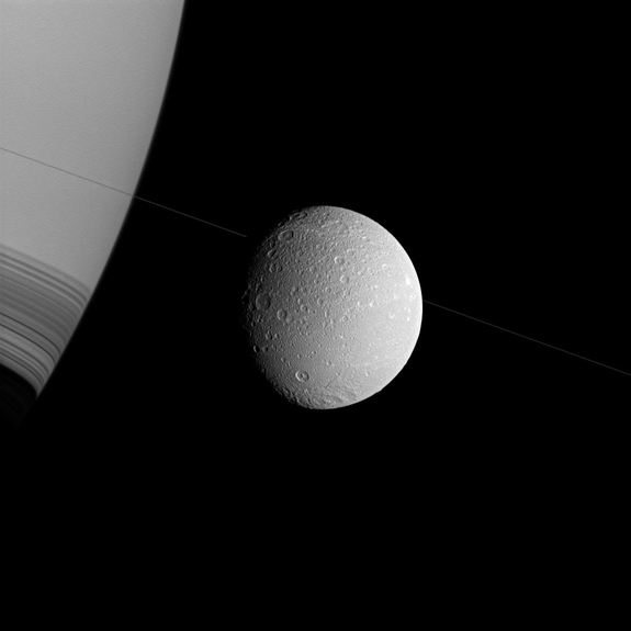 Saturn and Dione appear askew in this Cassini spacecraft view, with the north poles rotated to the right, as if they were threaded along on the thin diagonal line of the planet's rings.
