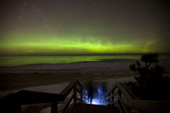 "Astrophotographer Shawn Malone took this image of an aurora Feb. 18, 2012. She said: ""A couple and their dog make their way down the beach stairs to check out the aurora borealis, over Lake Superior, Marquette MI. Can only wonder what the view must have been like from the passing plane pictured as a streak middle frame."""