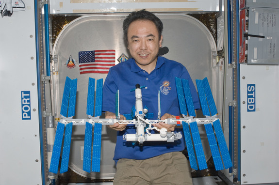 Japanese astronaut Satoshi Furukawa poses with the LEGO model of the International Space Station that he built on board the real space station.