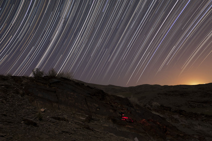 Star Trails Arc Over Ancient Landscape in Photo